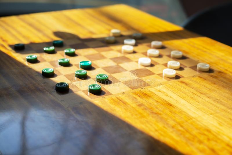 Wooden table with checkers in the games room.  stock photos