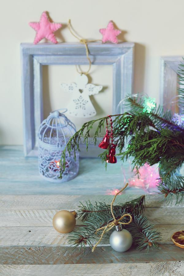 On a wooden table Christmas ball, cones, spruce branches, decorative lights, illumination. Decorate the interior for seasonal winter holidays royalty free stock photo