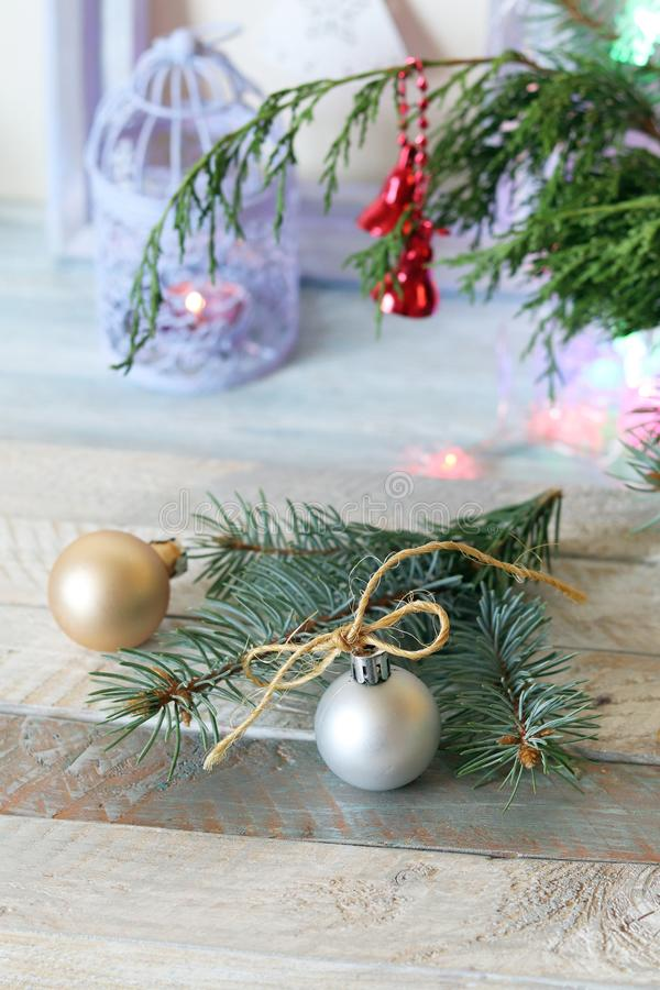 On a wooden table Christmas ball, cones, spruce branches, decorative lights, illumination. Decorate the interior for seasonal winter holidays royalty free stock image