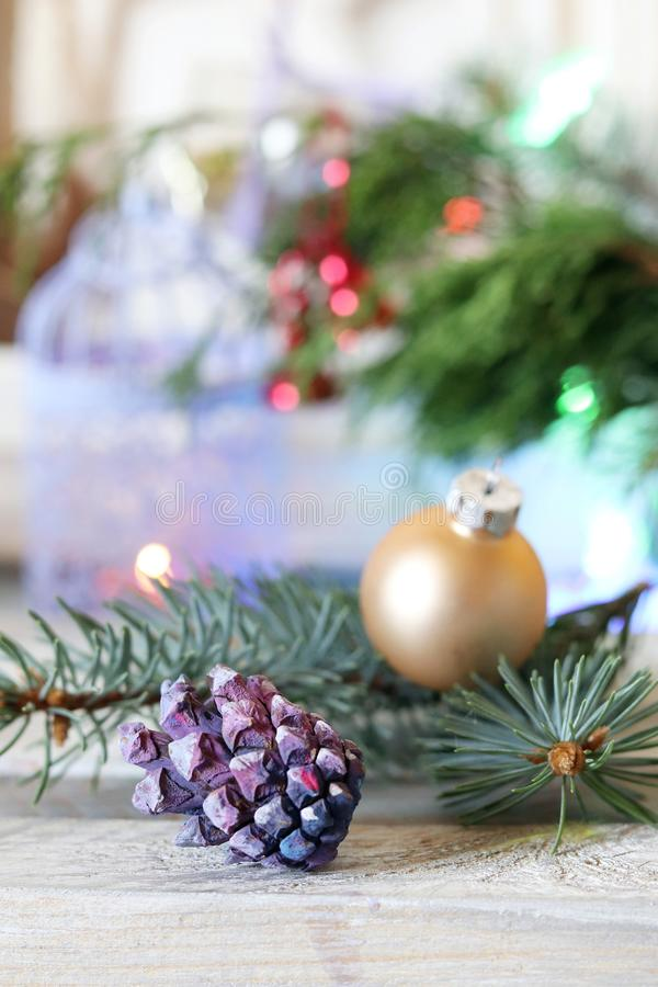 On a wooden table Christmas ball, cones, spruce branches, decorative lights, illumination. Decorate the interior for seasonal winter holidays stock photos
