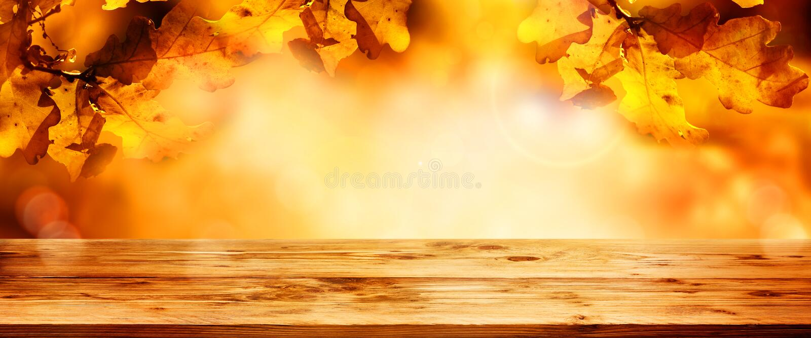 Wooden table with colorful autumn leaves stock photo