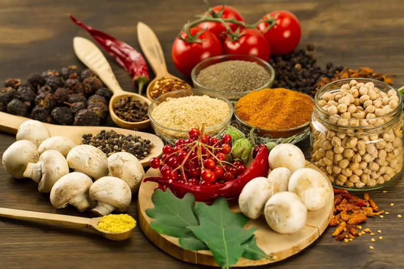 Wooden table with colorful spices, herbs and vegetables. stock photo