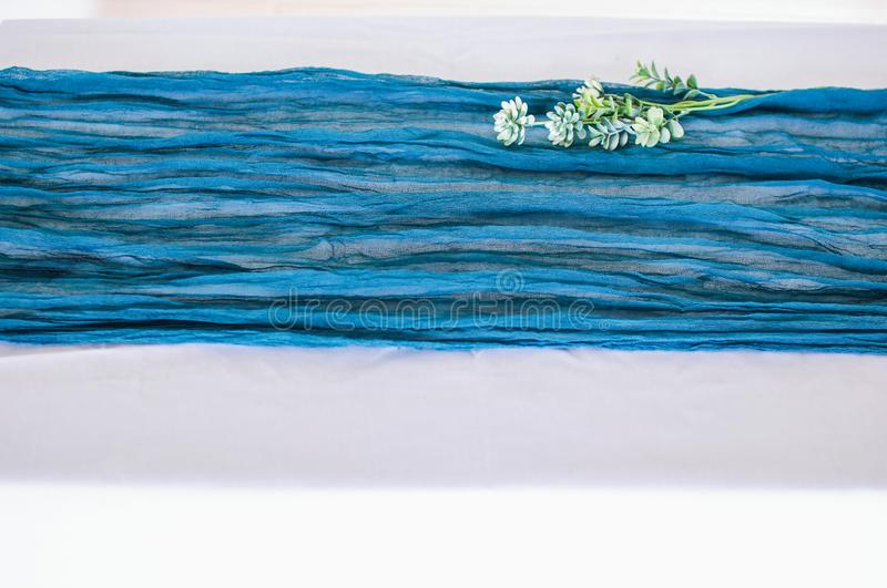Blue gauze runner for weddings events. Wooden table is covered with a color runner tablecloth with a white plate and cutlery stock image