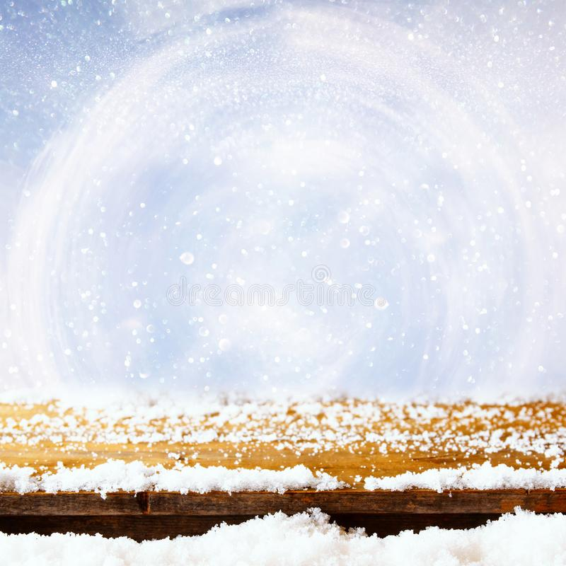 wooden table covered with snow in front of glitter lights royalty free stock images