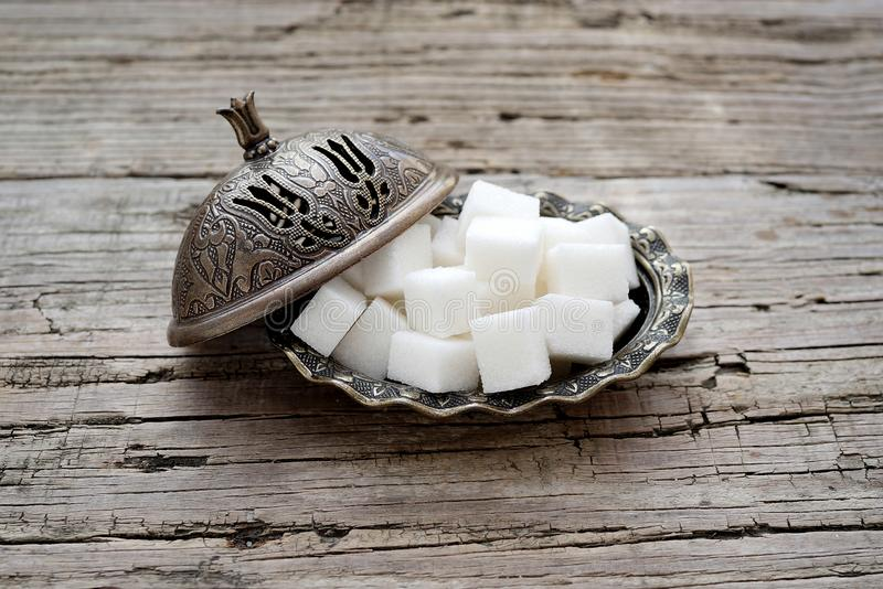 Cube sugar in bowl. Wooden table, cube sugar in bowl stock image