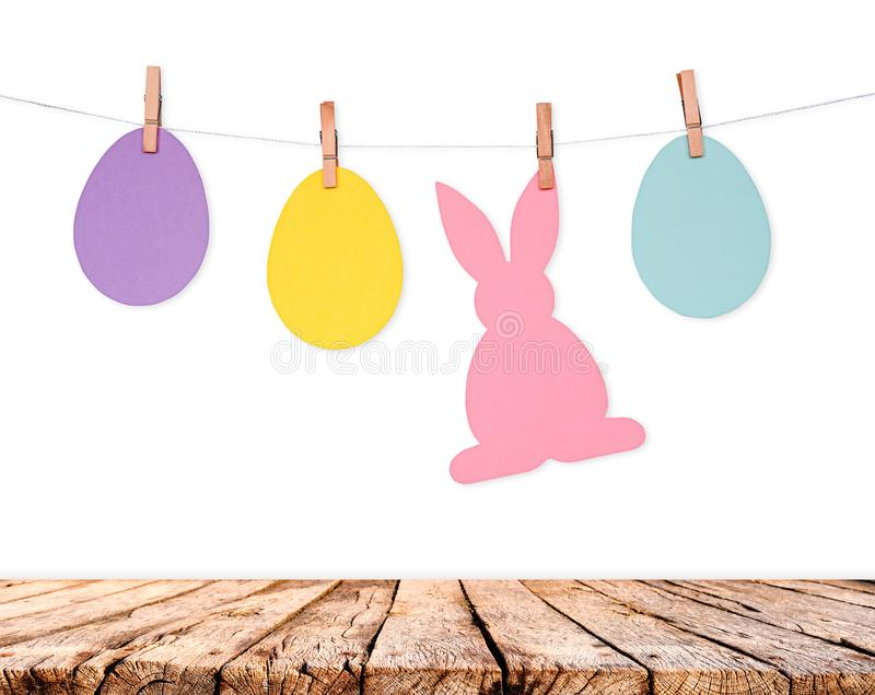 Wooden table and eggs and rabbits decoration garland on white wall. Easter holiday background stock photos
