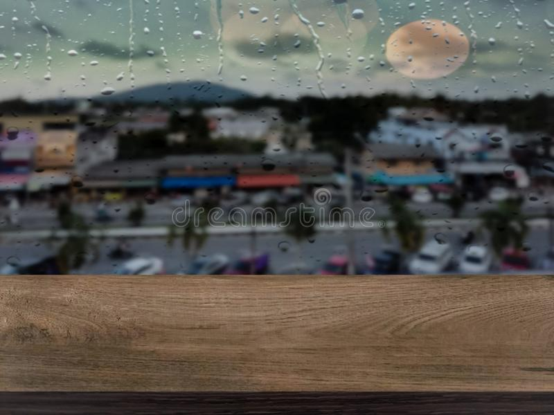 Wooden table floor with a window atmosphere when it rains. Wooden table floor window atmosphere rains water drop raining bokeh light dark city clouds sky stock image