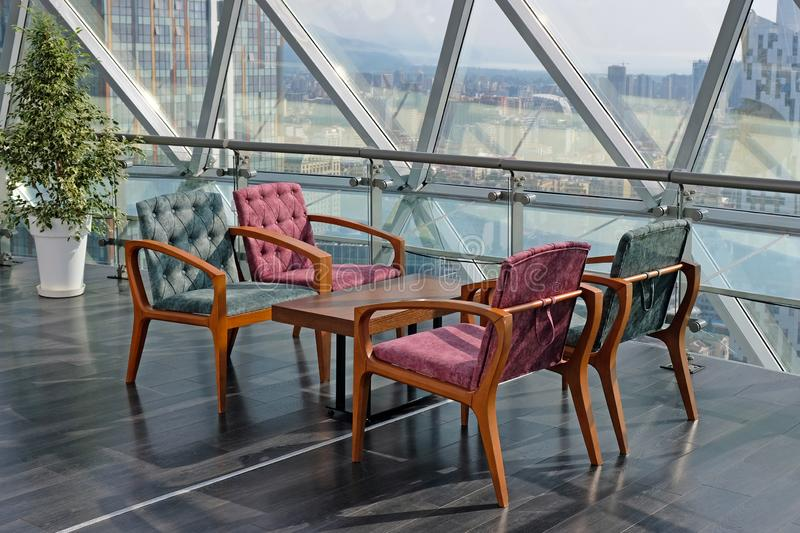 Wooden table and four soft chairs. Stylish interior in a cafe. Modern living room furniture. A place to relax with panoramic city views stock photo
