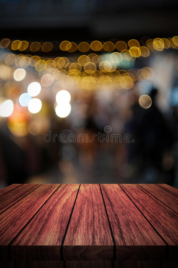 Wooden table in front of abstract blurred background stock photography