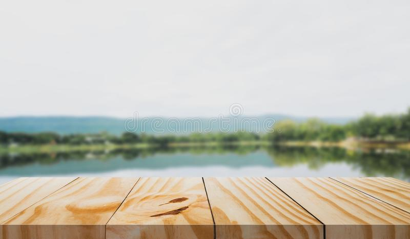 Wooden table in front and blur of nature background.  royalty free stock image