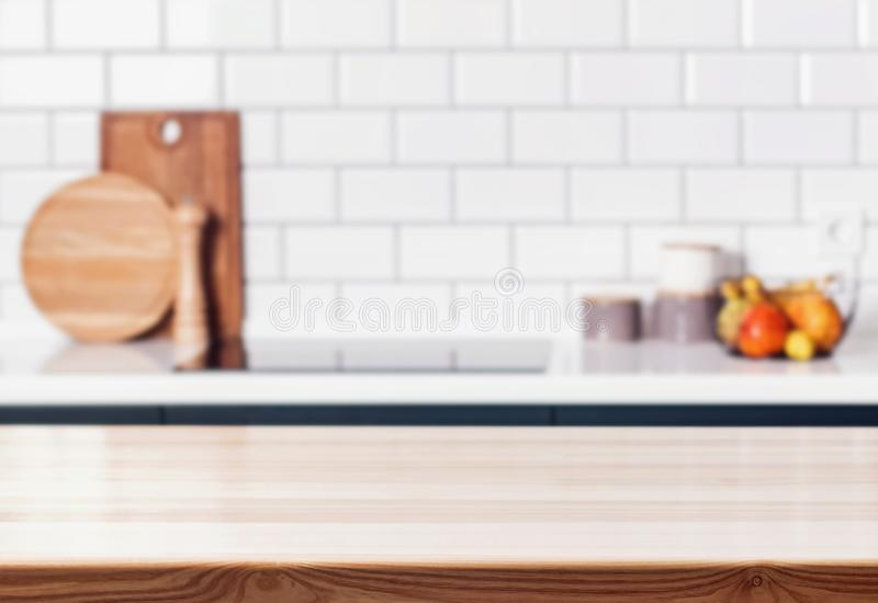 Wooden table in front of blurred modern kitchen. royalty free stock photo