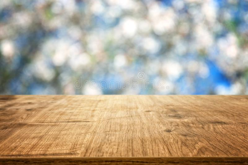 Wooden table in front of spring blossom tree landscape. Product display and presentation. Wooden table in front of spring blossom tree landscape. Product stock photography