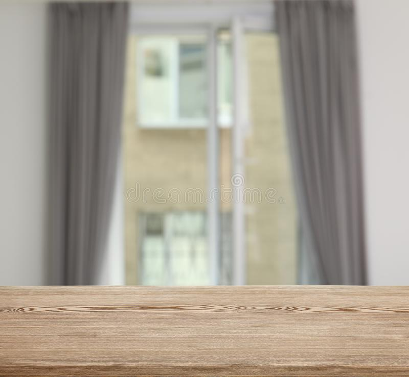 Wooden table in front of window with curtains. Indoors stock images