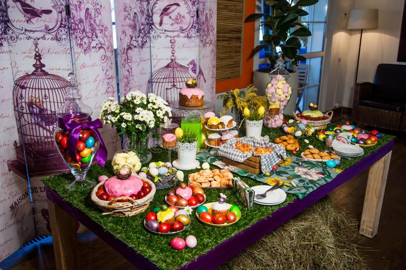 A wooden table with a grassy tablecloth and Easter treats: eggs, cakes, chocolate eggs, meringues stock images