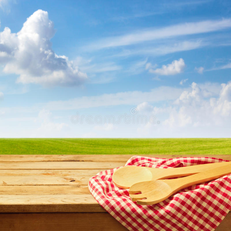Wooden table with kitchen utensil over green meadow and blue sky stock photo