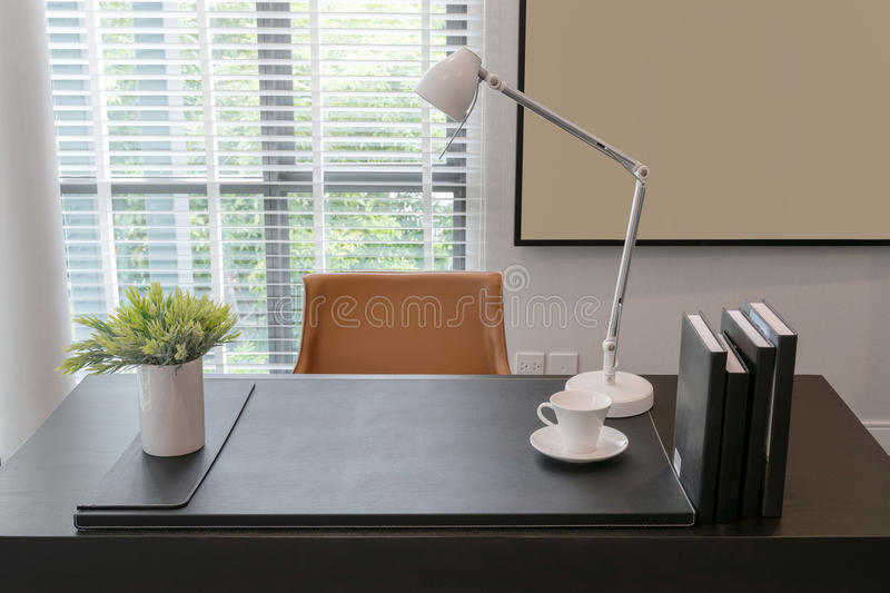 Wooden table with lamp and books in modern working room royalty free stock images