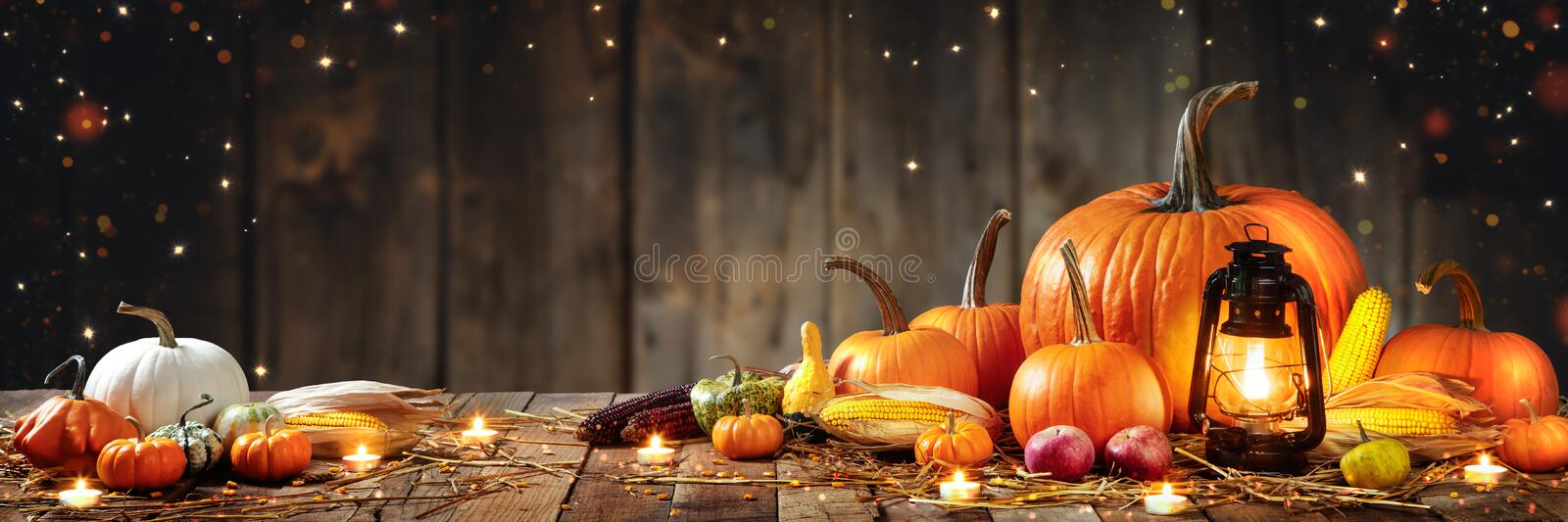 Table With Lantern And Candles Decorated With Pumpkins, Corncobs, Apples And Gourds stock photography