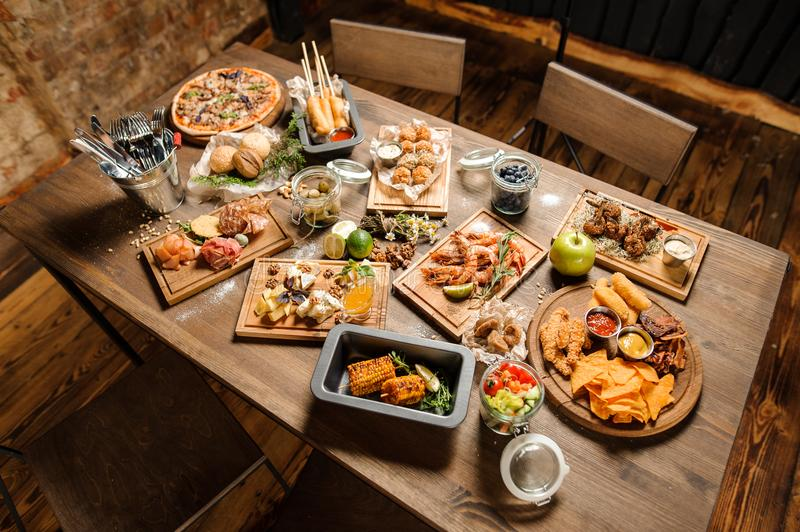 Wooden table with a large amount of tasty dishes. Wooden table with a large amount of tasty homemade dishes on the cozy indoors background royalty free stock photography
