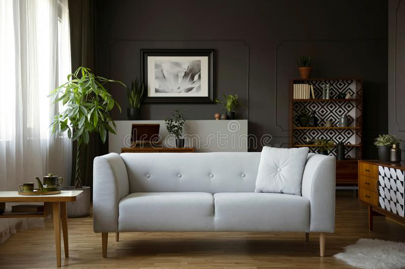Wooden table next to grey sofa in dark living room interior with poster and plants. Real photo stock image