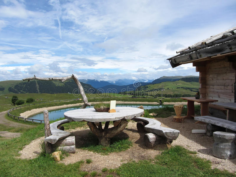 Wooden table next to hut cabin in mountain alps . Panoramic mountain view of the Dolomites in background . Alpe di Siusi, South Ty stock image