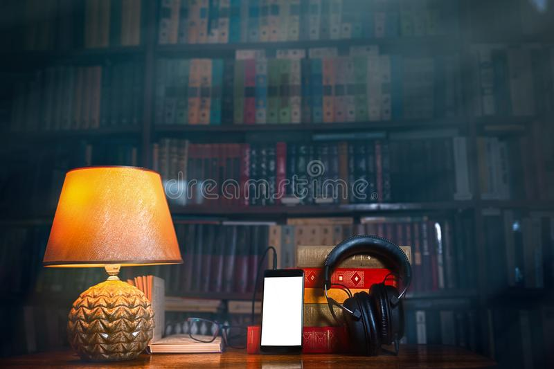 On a wooden table next to the lamp are headphones, a phone, a stack of books and glasses. The concept of modern technology and royalty free stock images