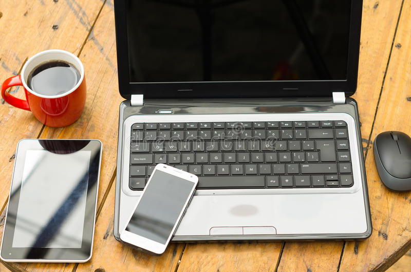 Wooden table with open laptop, mobile, tablet and. Red coffee mug royalty free stock images
