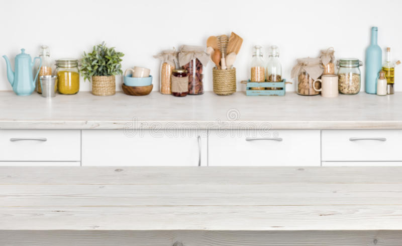 Wooden table over blurred kitchen furniture shelf with food ingredients. Wooden table over blurred kitchen furniture shelf with various food ingredients royalty free stock image