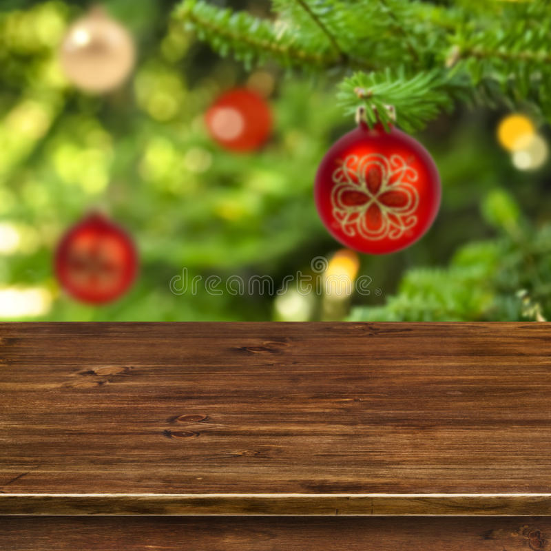 Wooden table on red Christmas ball background royalty free stock image