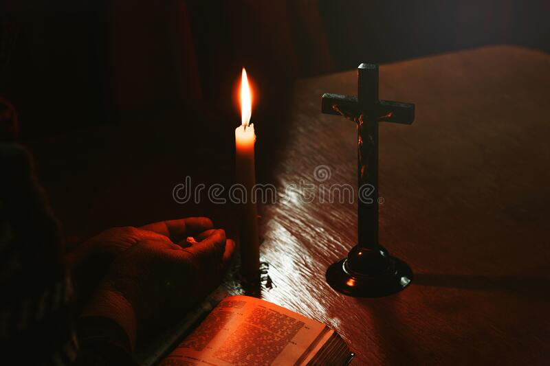 Wooden table in retro style. On it is a candle and a cross. Hands of an old woman over a book. Palms folded stock photos