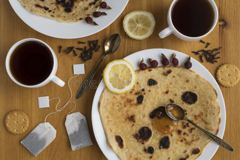 Wooden table with round cakes on plates and two cups of tea royalty free stock photos