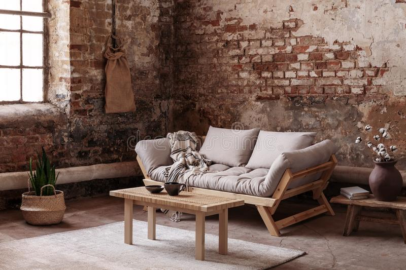 Wooden table on rug in front of beige couch in apartment interior in wabi sabi style with red brick wall. Real photo stock photos