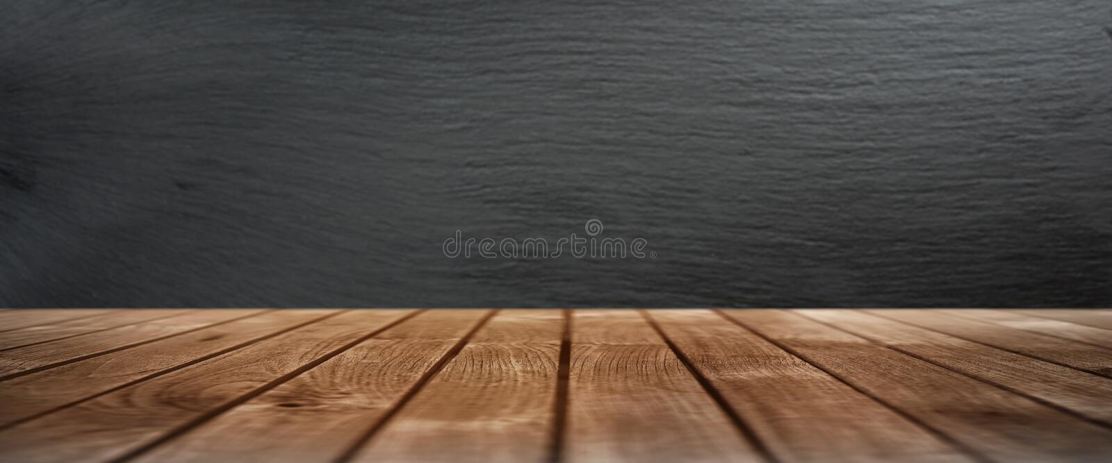 Wooden table with a slate wall. Rustic wooden table in front of a wall from slate for a decoration royalty free stock photos