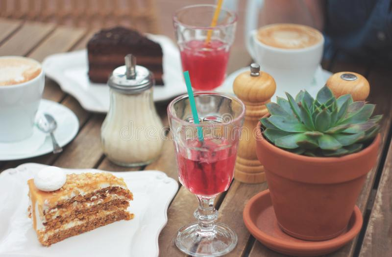 Wooden table on summer terrace with cake, berry juice, succulent royalty free stock photos