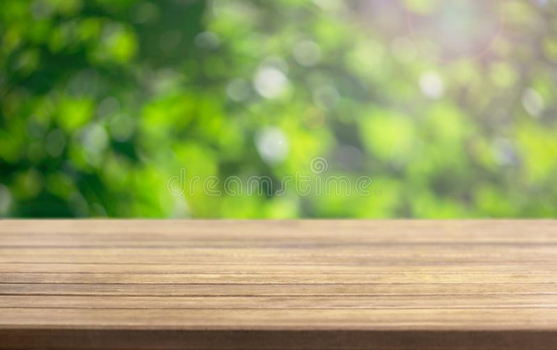 Wooden table surface and blurred leaves of a tree in the background stock photos