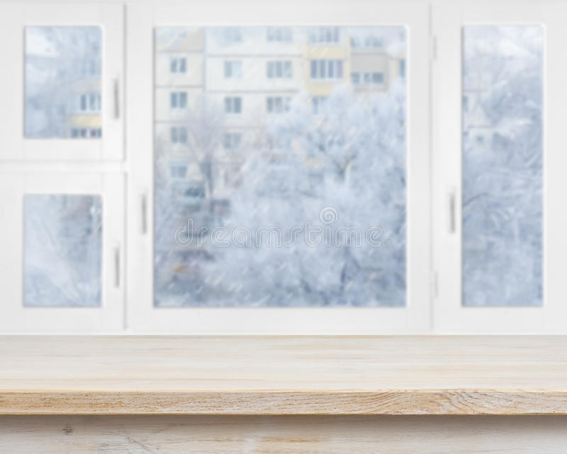 Wooden table surface over frosty window background stock photo