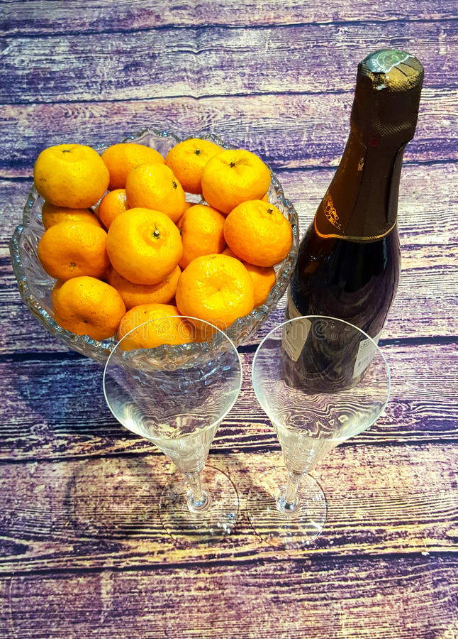 On a wooden table tangerines in a crystal vase, wine glasses and a bottle of champagne. Romantic set - on a wooden table tangerines in a crystal vase, wine stock photo