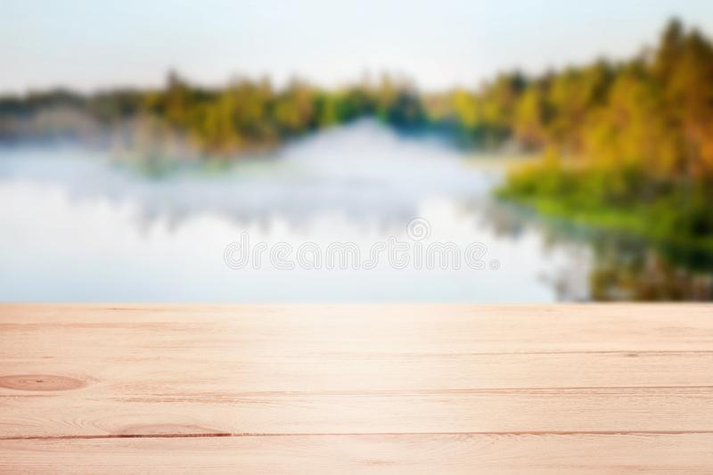 Wooden table template with distant defocused forest lake background royalty free stock photography