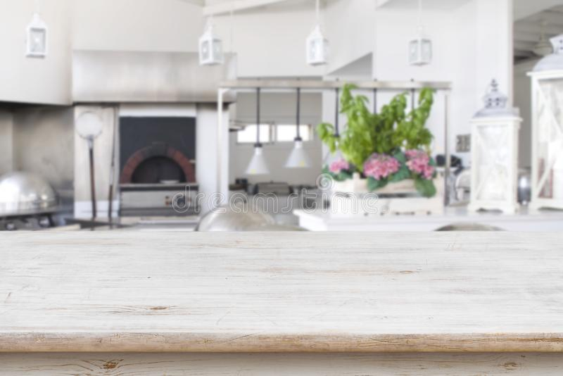 Wooden table top on blurred modern restaurant kitchen room background.  stock photos