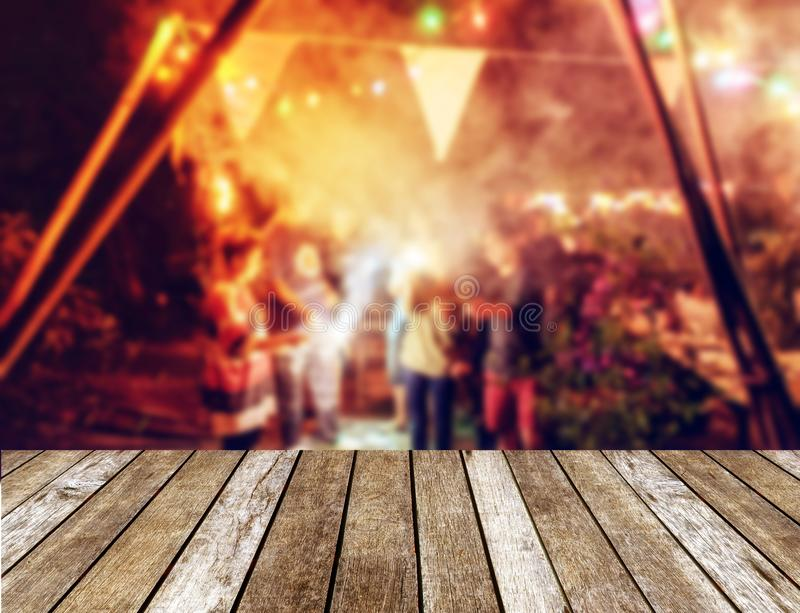 Wooden table top on blurred new year celebration friends party w royalty free stock photography