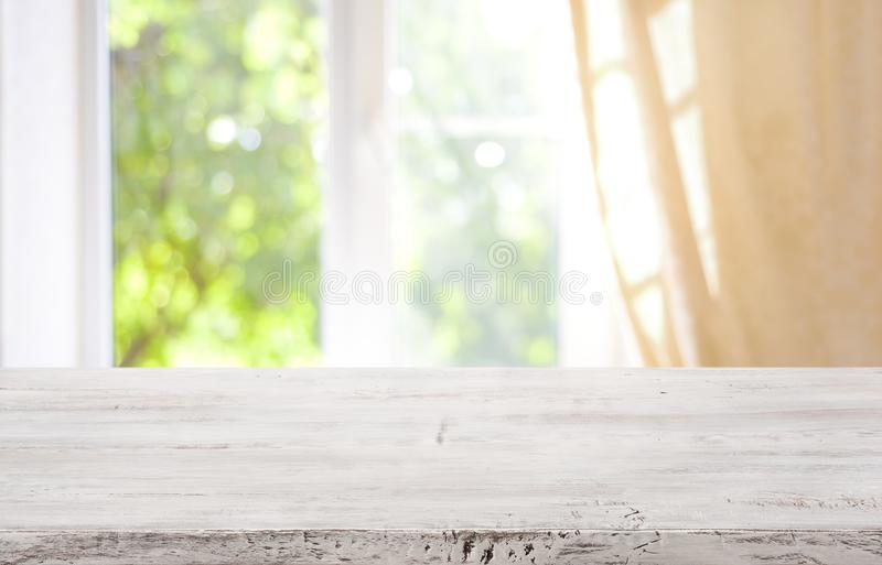 Wooden table top on blurred window background for product display.  stock photography