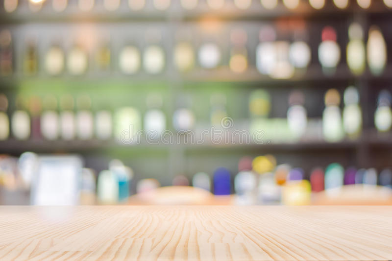 Wooden Table Top with Blurred Wine Liquor bottles Display Background royalty free stock photo