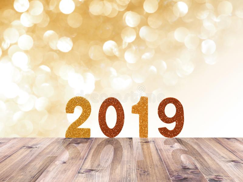 Wooden table top and 2019 New year glitter number over gold abstract blured background and white bokeh for Christmas or new year stock photography