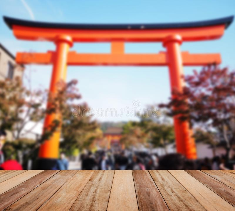 Wooden table top over blur background of Japanese red torii main gate stock images