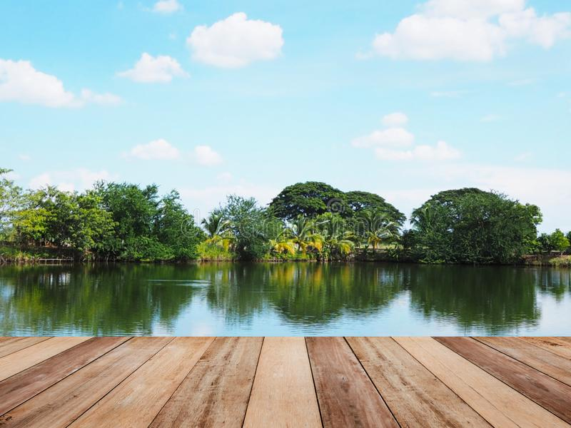 Wooden table top over blurry background of fishing pond with ref. Lection of blue sky. Montage style to display the product stock images