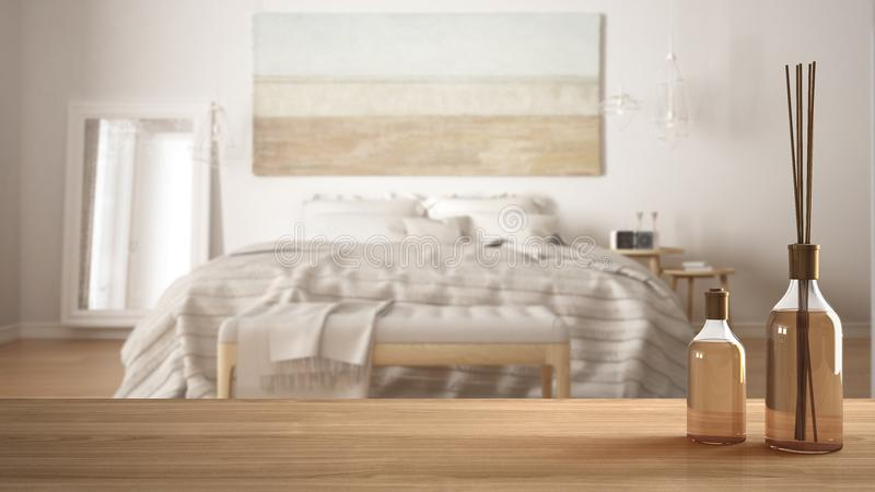 Wooden table top or shelf with aromatic sticks bottles over blurred modern bedroom with classic bed, white architecture interior d royalty free stock photos