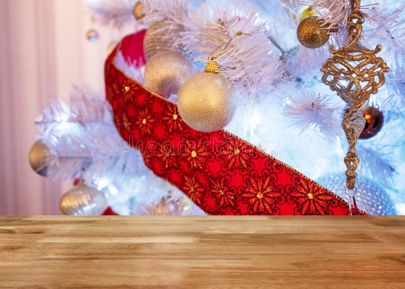 Wooden table top on white christmas tree illumination stock images