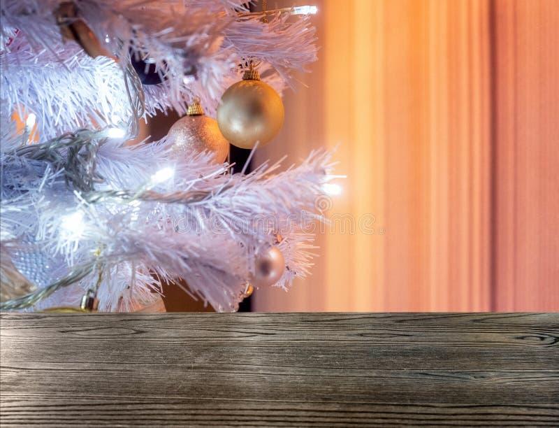 Wooden table top on white christmas tree illumination stock photography