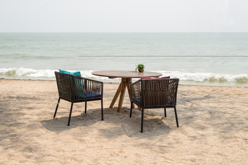 Wooden table with two chairs at beach restaurant stock photography