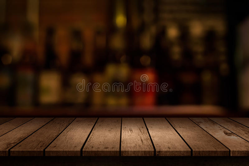 Wooden table with a view of blurred beverages bar. Backdrop