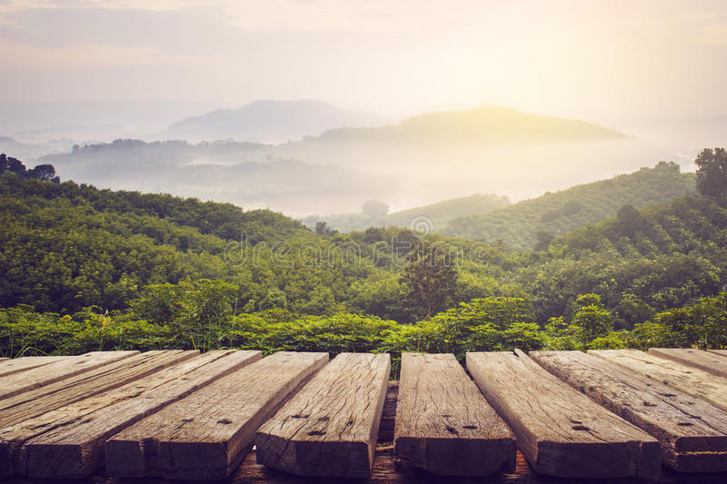 Wooden table and view of mountain with sun light. Vintage process picture royalty free stock photo
